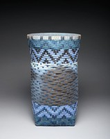 Vertical woven paper basket with round mouth and square bottom, in Cherokee water pattern; paper dyed shades of blue, lavender, and black. Photograph of Tuckasegee River in central band; text written on paper weaving strips drawn from David Archimbault's speech to United Nations in response to Dakota Access Pipieline on Standing Rock Sioux Reservation.