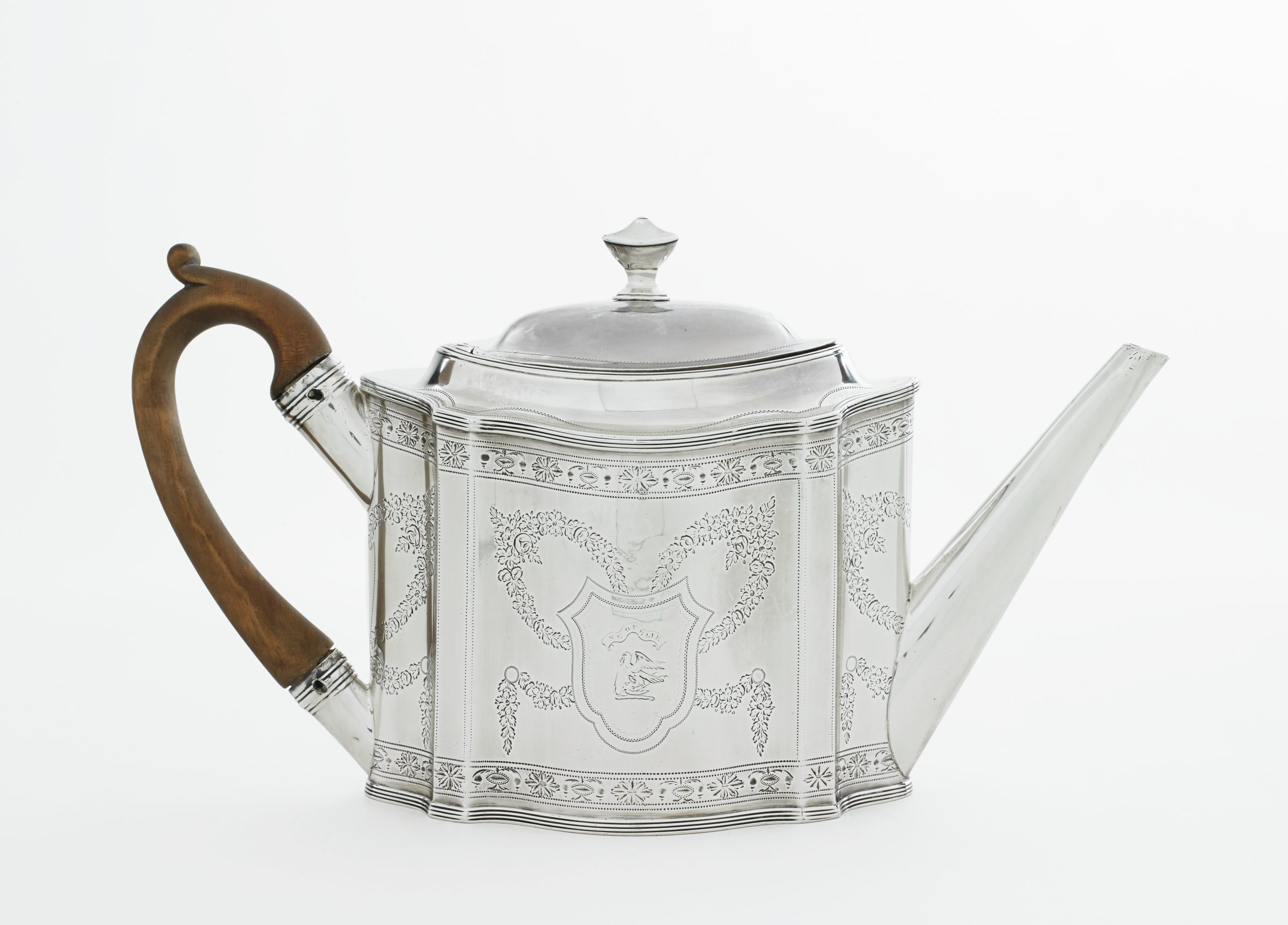 Small oval teapot of sterling silver, the body with serpentine sides, a flat shoulder and raised neck into which fits the domed cover with a finial in the shape of a covered urn, the spout is long and straight, the ear-shaped handle of teakwood with a slightly scrolled thumb rest, the sides are decorated with bright-cut engraving in a pattern of floral garlands surrounding a central shield with on one side a bird with outstretched wings below a banner, the other shield empty, the upper and lower body decorated with a band of stylized floral elements.